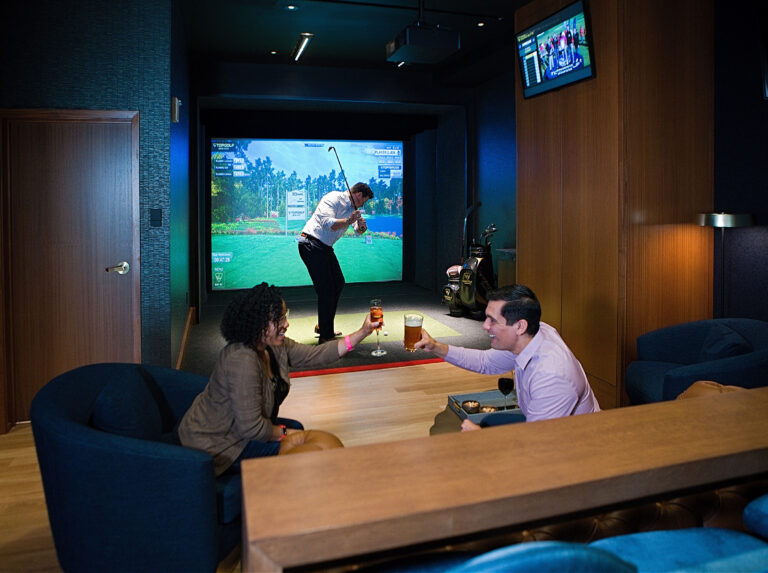 Top Golf suite with a man playing their golf VR game